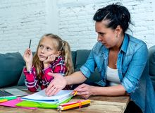 Mutter, die mit Tochter frustriert wird, während, die Hausarbeit tuend, die zu Hause auf Sofa bei der Lernschwierigkeitenhausarbe lizenzfreie stockfotografie