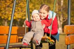 Mutter, die mit Tochter im Park schwingt Stockfotografie