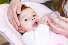 Mutter, die neugeborene Tochter mit Saugflasche einzieht Lizenzfreies Stockbild