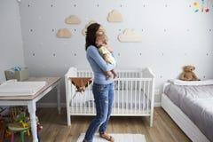 Mutter, die neugeborenen Baby-Sohn in der Kindertagesstätte tröstet lizenzfreie stockbilder