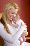 Mutter, die neugeborenes Schätzchen in Schwingstuhl anhält Lizenzfreies Stockfoto