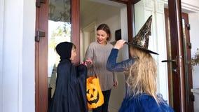 Mutter, die oben Kinder an Trick-oder-Behandlungsweg Halloween-Feiertag für Kinder kleidet lizenzfreies stockfoto