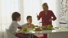 Mutter, die Pfannkuchen für zwei Jungen brät Jungen, die frühstücken stock footage