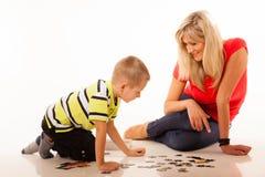 Mutter, die Puzzlespielspielzeug mit ihrem Sohn spielt Lizenzfreie Stockfotos