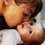 Mutter, die Schätzchen küßt lizenzfreie stockfotos