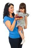 Mutter, die scharfe Frucht ihrer Tochter anbietet Stockfotografie