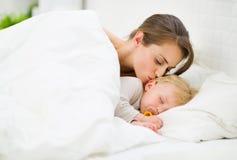 Mutter, die schlafendes Schätzchen küßt Lizenzfreie Stockfotos
