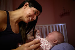 Mutter, die schreiendes Baby in der Kindertagesstätte tröstet Stockbild