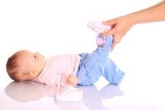 Mutter, die Schuhe auf Schätzchen setzt Stockbilder