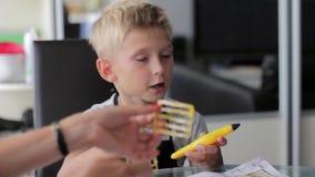 Mutter, die seinem Sohn hilft, seine Hausarbeit zu tun stock video footage