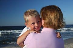 Mutter, die Sohn auf einem Strand umarmt Stockfotografie