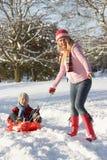 Mutter, die Sohn auf Schlitten durch Snowy Landsca zieht Stockfoto