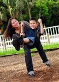 Mutter, die Sohn auf Schwingen drückt Stockfotos