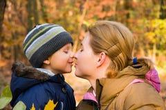 Mutter, die Sohn in der Herbstlandschaft küßt Stockfoto