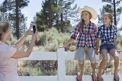 Mutter, die Töchter durch Handy fotografiert, wie sie auf Zaun am Park sitzen Lizenzfreie Stockfotografie
