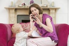 Mutter, die Telefon im Wohnzimmer mit Schätzchen verwendet Lizenzfreie Stockfotos