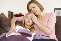 Mutter, die Temperatur der kranken Tochter nimmt Stockbilder