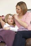 Mutter, die Temperatur der kranken Tochter nimmt Stockbild