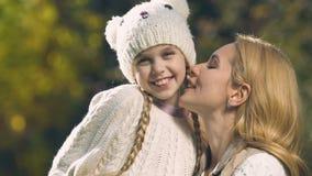 Mutter, die Tochter auf Backe, extrem glückliches Mädchen lächelt an der Kamera im Park küsst stock video