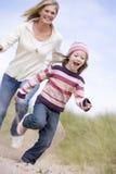Mutter, die Tochter durch Sanddünen jagt Lizenzfreies Stockbild