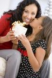 Mutter, die Tochter ihr Weihnachtsgeschenk gibt Lizenzfreies Stockfoto