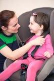 Mutter, die Tochter im Autositz, lokalisiert sichert stockfotografie