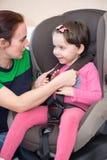 Mutter, die Tochter im Autositz sichert, lizenzfreie stockbilder