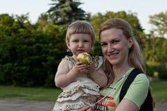 Mutter, die Tochter mit Apfel hält Lizenzfreies Stockfoto
