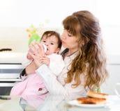 Mutter, die trauriges Baby mit Saugflasche einzieht Lizenzfreie Stockfotografie