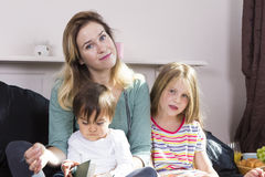 Mutter, die zu den Kindern im Bett liest lizenzfreie stockfotos