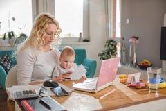 Mutter, die zu Hause Büro mit ihrem Baby bearbeitet Stockfoto