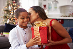 Mutter, die zu Hause dem Sohn Weihnachtsgeschenke gibt Lizenzfreies Stockfoto