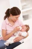 Mutter, die zu Hause Flaschen-Baby gibt lizenzfreie stockbilder