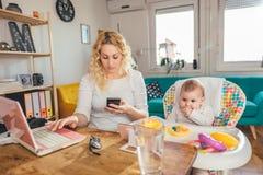 Mutter, die zu Hause intelligentes Büro des Telefons mit ihrem Baby verwendet Stockfotos