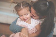 Mutter, die zu Hause mit ihrer Tochter genießt stockbilder