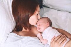 Mutter, die zu Hause neugeborenes Baby stillt Lizenzfreie Stockbilder