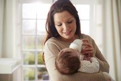 Mutter, die zu Hause neugeborenes Baby von der Flasche einzieht Lizenzfreie Stockfotos