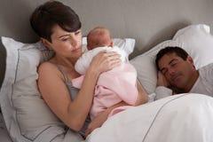 Mutter, die zu Hause neugeborenes Schätzchen im Bett streichelt Lizenzfreie Stockbilder