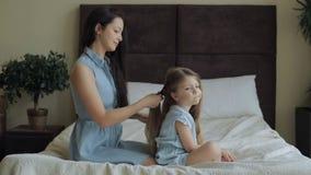 Mutter, die zu Hause Tochterhaar auf Bett kämmt stock video