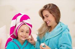Mutter, die zu ihrer kleinen Tochter eine Creme im Gesicht, Tragen blaue Bademäntel im Raum aplying ist stockfoto