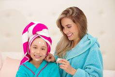 Mutter, die zu ihrer kleinen Tochter eine Creme im Gesicht, Tragen blaue Bademäntel im Raum aplying ist lizenzfreies stockbild