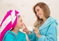 Mutter, die zu ihrer kleinen Tochter eine Creme im Gesicht, Tragen blaue Bademäntel im Raum aplying ist lizenzfreie stockfotos