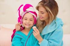 Mutter, die zu ihrer kleinen Tochter eine Creme im Gesicht, Tragen blaue Bademäntel im Raum aplying ist lizenzfreie stockfotografie