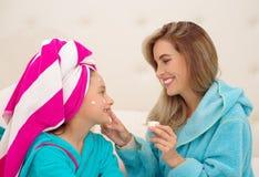Mutter, die zu ihrer kleinen Tochter eine Creme im Gesicht, Tragen blaue Bademäntel im Raum aplying ist lizenzfreies stockfoto