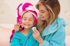 Mutter, die zu ihrer kleinen Tochter eine Creme im Gesicht, Tragen blaue Bademäntel im Raum aplying ist stockbilder