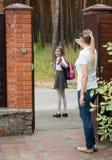 Mutter, die zu ihrer Tochter in der Schule geht wellenartig bewegt Lizenzfreie Stockfotografie
