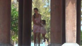 Mutter dreht sich in seine Armtochter in einem schönen buddhistischen Gebäude mit Spalten stock footage