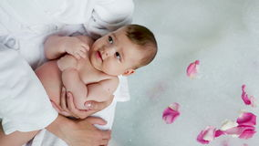 Mutter in einem Bademantel, der ein Baby in den Händen hält stock video