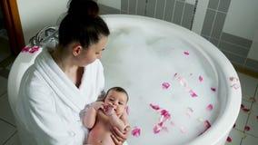 Mutter in einem Bademantel, der ein Baby in den Händen hält stock footage