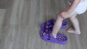 Mutter entfernt ihre Turnschuhe von den erwachsenen Füßen, setzt ein kleines Kind erwachsene Turnschuhe auf Kind-` s Füße und geh stock video
